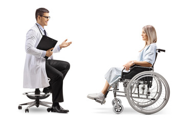 Male doctor sitting and talking to a young female patient in a wheelchair
