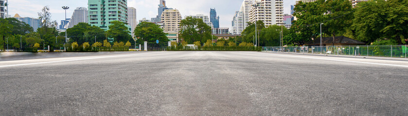 Empty asphalt road with city in the background