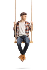 Male student on a wooden swing looking to the side
