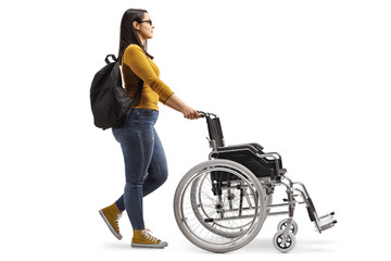 Female student pushing an empty wheelchair
