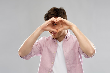 love, charity and valentine's day concept - smiling man making hand heart gesture over grey background