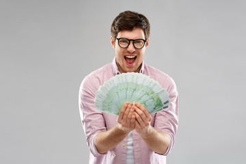 money, finance, business and people concept - happy young man in glasses with fan of one hundred euro bank notes over grey background