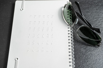 Braille dots - reading without seeing.braille alphabet at the back of notebook