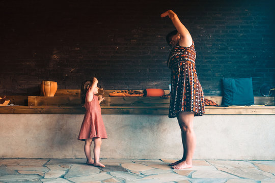 mother and daughter do gymnastics and yoga together. child learn from adult. family time and connection between generations concept