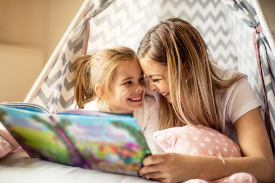 Mother reading a story to her daughter.