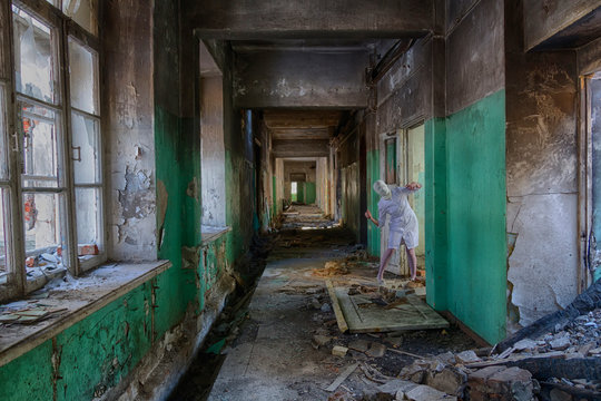 Nurse without face (head bandaged) zombie with a knife in abandoned hospital or an insane asylum. Maybe picture for horror movie