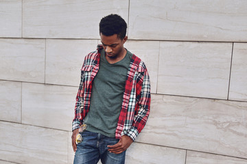 Wall Mural - Stylish african man wearing red plaid shirt looking down, young guy posing on city street, gray brick wall background