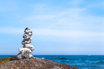 Small natural Tower of Stones at Sea / Stack of stones in balance at rock on coast of baltic sea (copy space)