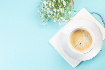 Good morning concept - coffee, flowers, notebook, blue background top view