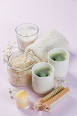 SPA concept - towel, salt, candle on pink background, copy space