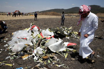 A Saudi man who's brother died in the Ethiopian Airlines Flight ET 302 plane crash, watches debris after a commemoration ceremony at the scene of the crash, near the town of Bishoftu, southeast of Addis Ababa