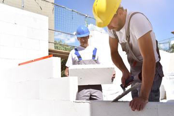 Bauarbeiter-Maurer auf einer Naustelle beim Hausbau // teamwork on the building site - construction workers build a family home