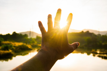 Use hand to touch the sun light in the morning, Pick up the sun by hand, Close the sun in your hand, Yellow light with cold air in winter, Flare from sunrise, Symbols of hope