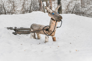 A wooden yellow horse or donkey with a carriage for children on the playground in the winter park