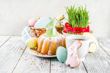 Easter table setting concept, festive table with decoration of young grass, cake, pastel colored...
