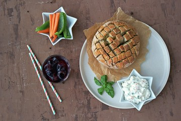 Party set on a brown concrete background: baked party bread with herbs and olive oil, a dip of cream cheese with vegetables, sliced raw carrots and green sweet pepper, grape juice with ice, straw.
