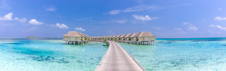 Landscape of Maldives beach. Tropical panorama, luxury water villa resort with wooden pier or jetty. Luxury travel destination background for summer holiday and vacation concept Wall mural