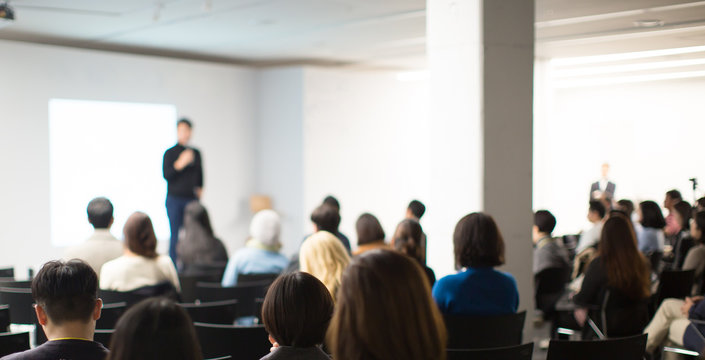 """""""Speaker on Stage at Conference Meeting Event. Presenter at Business Seminar Photo. Audience Watching a Manager Presentation. Blurred Image of Lecturer Presenting To Audience During Speech. """""""