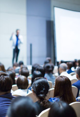 """Speaker on Stage at Conference Meeting Event. Presenter at Business Seminar Photo. Audience Watching a Manager Presentation. Blurred Image of Lecturer Presenting To Audience During Speech. """