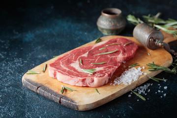 Fresh raw beef steak on wooden board.