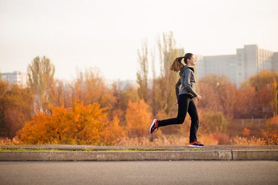 Woman running in autumn fall forest. Healthy concept