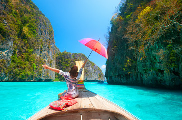 Joyful woman with umbrella travels in summer clothes on a boat among the islands of Phi Phi in Thailand