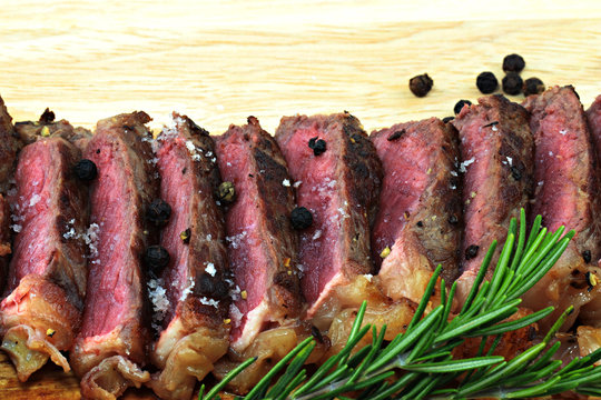Medium Beef Rib Eye steak slices on wooden board