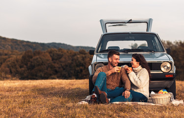 Beautiful young couple enjoying picnic time on the sunset. They drinking tea and sitting in a meadow leaning against a old fashioned car. Wall mural