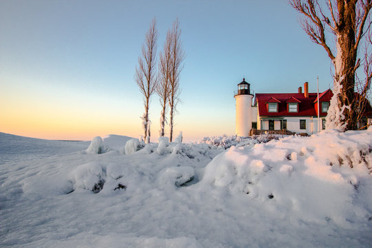 Winter Lighthouse On The Great Lakes. Beautiful winter landscape on the  coast of Lake Michigan with the Point Betsie Lighthouse bathed in the glow of the setting sun.