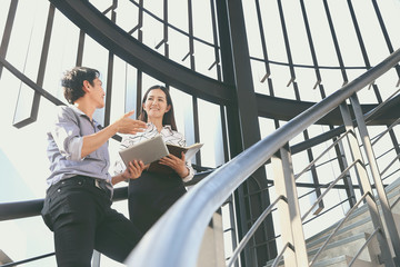 Two businessmen, men and women are talking about business plans. On the stairs in a modern building
