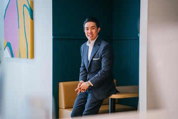 A young, attractive and masculine professional Chinese Asian man leaning against a table as he smiles confidently with his hands crossed. He is wearing a business coat and pants.