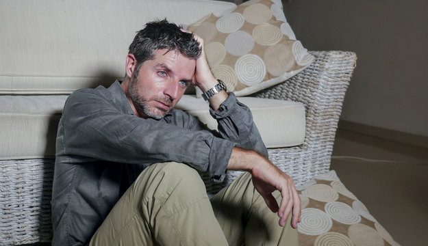 lifestyle portrait young attractive sad and depressed man sitting on living room floor feeling desperate and stressed suffering depression and anxiety problem looking frustrated