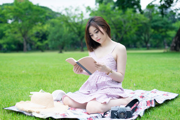 Young Asian woman is reading a book in the park during holiday relaxation concept.