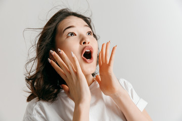 Wow. Beautiful female half-length front portrait isolated on gray studio backgroud. Young emotional surprised asian woman standing with open mouth. Human emotions, facial expression concept.