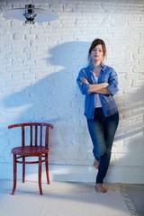 Casual woman standing against wall
