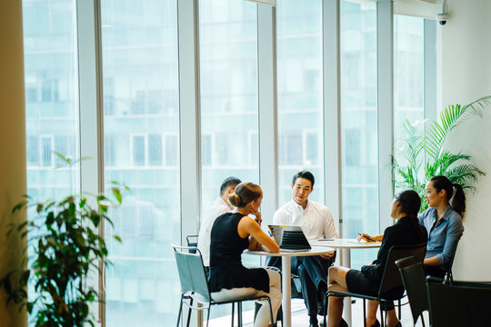 A diverse team sits around a table in a meeting room to have a business meeting to discuss plans. The group is international with Asian and white team members and they are all professionally dressed.