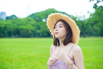 Young Asian woman is listening to music throuh head phone in the park.