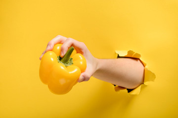 Hand taking a yellow pepper