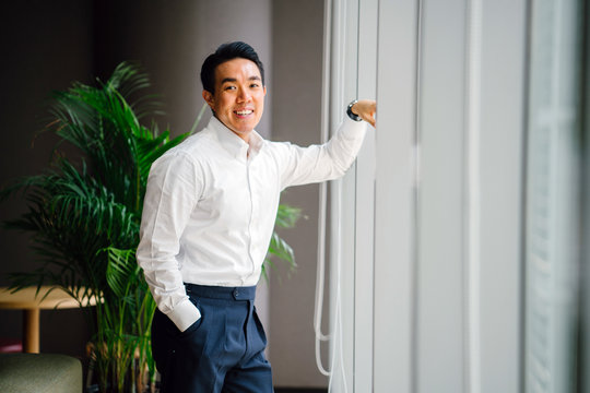 Portrait of a gorgeous young Asian businessman in a white shirt with green plants against a glass window during the day. He's relaxed, self-assured and smiling.