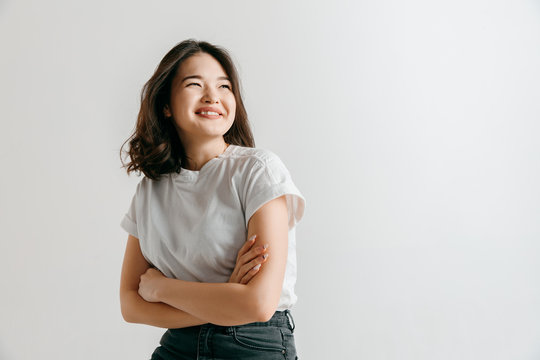 Happy asian woman standing and smiling isolated on gray studio background. Beautiful female half-length portrait. Young emotional woman. The human emotions, facial expression concept.