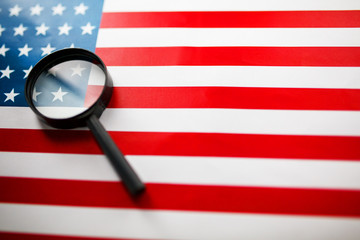 The American flag is viewed through a magnifying glass. Spies and surveillance USA concept. Control of the state of the United States