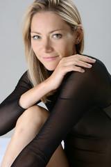 Beautiful slim blonde woman wears transparent lingerie as underwear or sleepwear in the studio