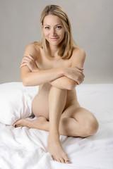 Portrait of a beautiful blond girl sitting nude in studio