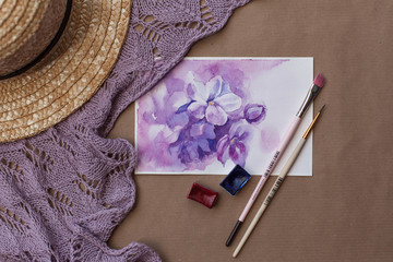 Watercolor postcard with purple flowers among brushes, paints, straw hat and knitted violet shawl. Hand drawn floral picture with lilac blooming in spring. Artistic flat lay. Romantic female concept.