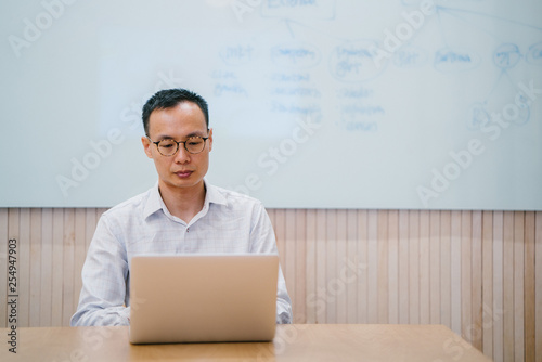 Portrait Of Relaxed Chinese Asian Businessman Sitting At A