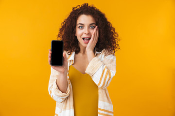 Image of caucasian woman 20s with curly hair holding and using selfie cell phone