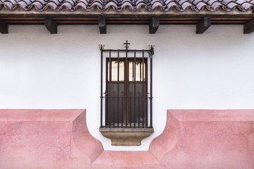 Caged window with cross decoration in Antigua, Guatemala