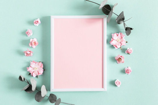 Flowers composition creative. Blank photo frame, pink flowers, eucalyptus branches on pastel mint background. Flat lay, top view, copy space