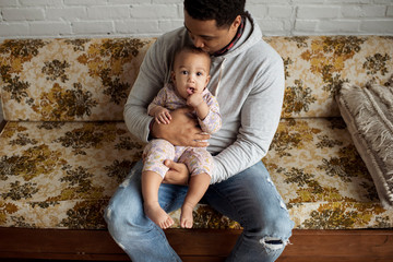 High angle view of father kissing on daughter's head while sitting in living room at home