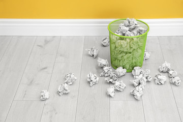 Metal bin with crumpled paper on floor near color wall, space for text